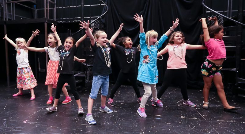 A group of young students stand on the theatre stage. Their arms are raised high and their faces are smiling broadly as they engage in a fun activity at one of our many KIDSTAGE classes & camps.