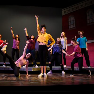 Theater arts students in Village Theatre's Institute program rehearse on stage.