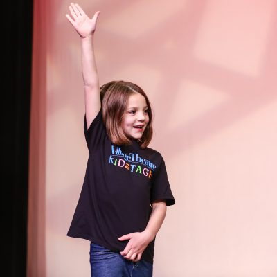 A child raises their hand to ask a question during one of Village Theatre's school programs.