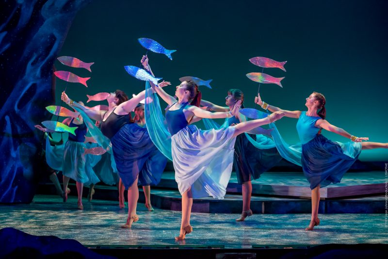 Dancers in blue and green hued dresses with their legs lifted back. They are carrying and lifting colorful fish to create a scene of underwater magic. The stage is lit with a blue light textured to also remind the viewer of water.