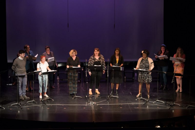 Performers in classy dress clothes behind microphones and music stands are reading and singing a new musical production on stage at First Stage Theatre in Issaquah.